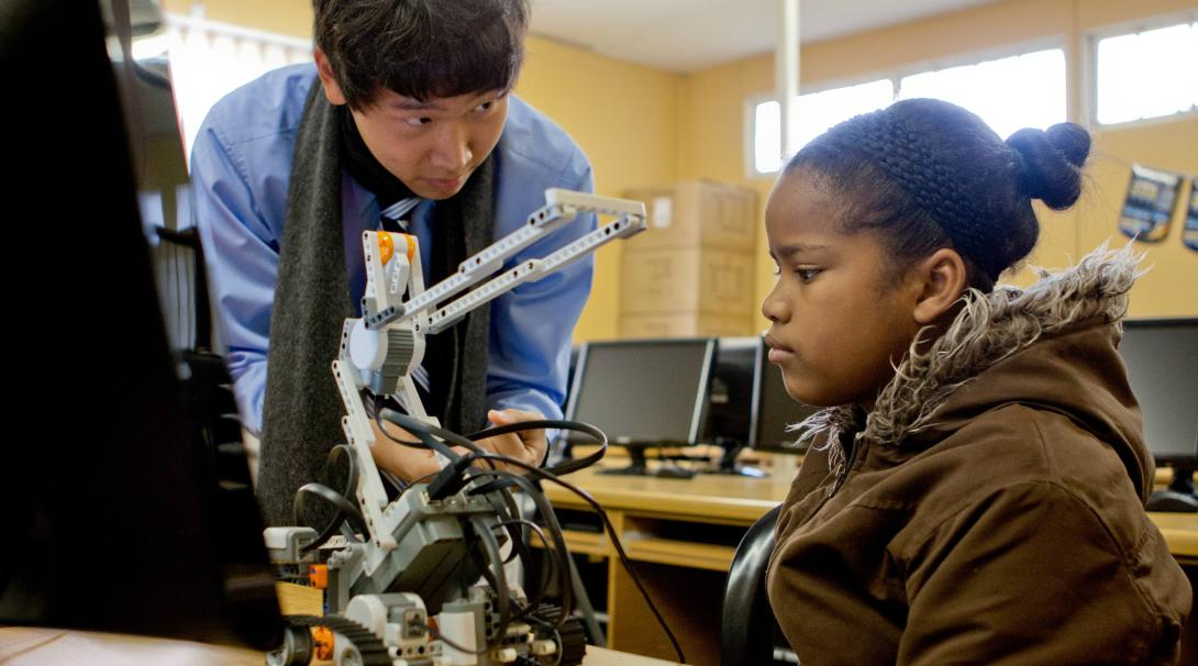 An IT teaching volunteer shows the functionality of a small robot to a girl in Ghana during his internship with Projects Abroad.